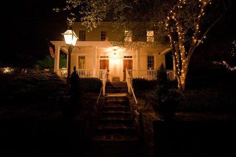The Riverdale Manor farm house at night.