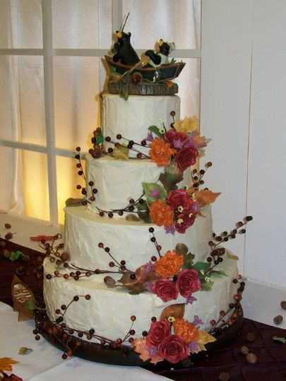 4 buttercream textured tiers adorned with hand made sugar flowers and berries.