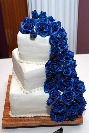Midnight blues sugar roses cascade down the three tier square cake.