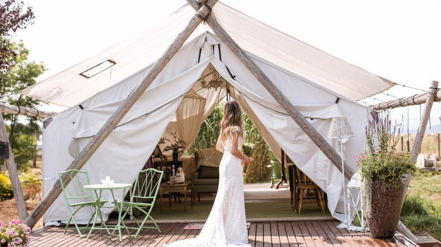 Bride poses with Glamping Tent