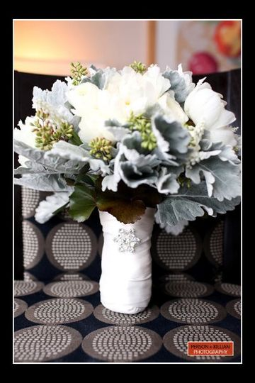 Wintery bouquet of white peonies & ranunculus and silver dusty miller. Handle accented with a...