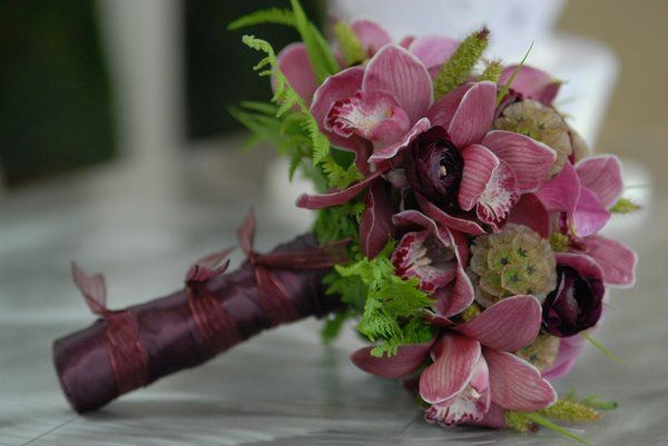 Burgundy bouquet with cymbidium orchid, calla lily, ranunculus, scabiosa pods and fern