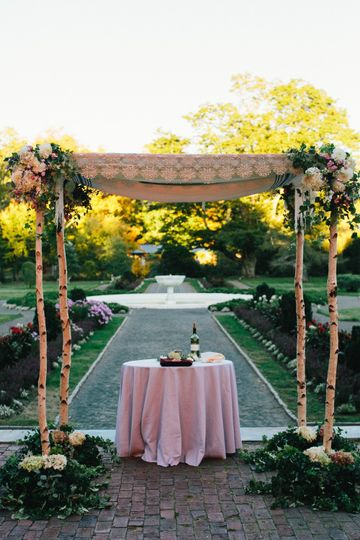 Birch pole chuppah with autumnal floral accents for garden ceremony