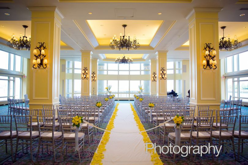Yellow rose petals border the aisle in hotel ballroom