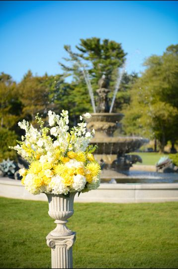 Classic urn arrangement with yellow and white summer  flowers for outdoor ceremony