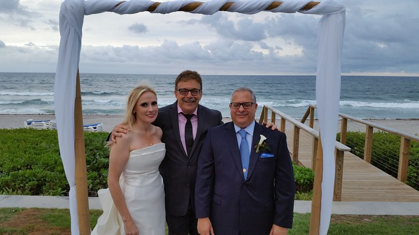 Newlyweds and the officiant by the beach