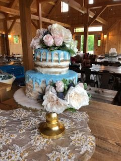 We placed these beautiful flowers on this simple naked cake with a pop of blue.