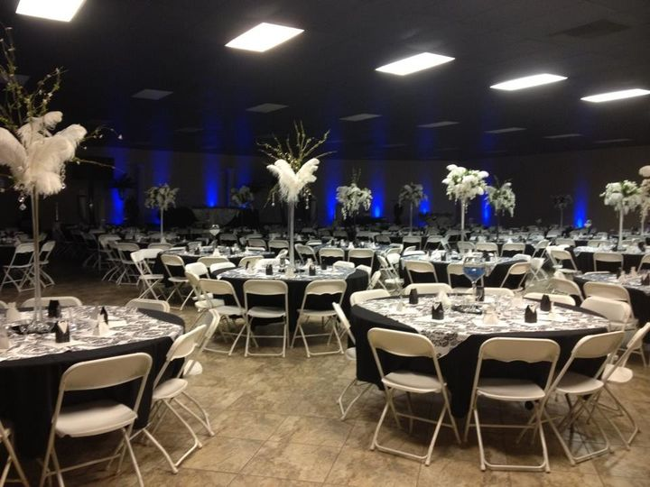 Main reception area. Features black and white design with centerpieces and blue uplights