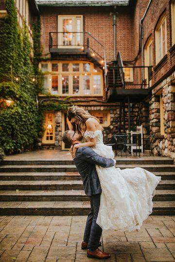 Bride and groom back of inn