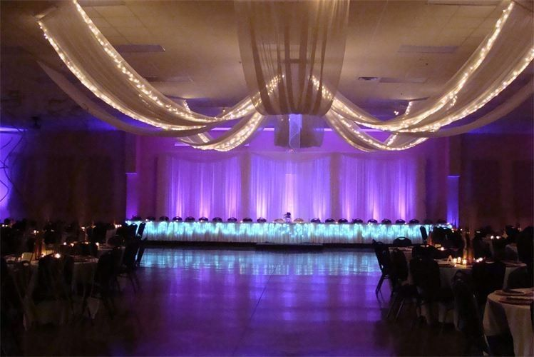 8 Legged Ceiling drapery that has been lit, 3 panel backdrop with up-lighting