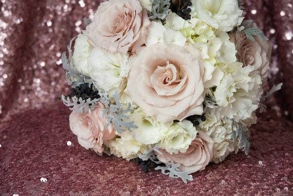 Bridal bouquet made of blush roses, white hydrangea, dusty miller, white lisianthus and navy blue...