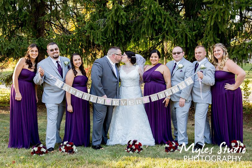 Wedding party formal portrait with a happily ever after sign.