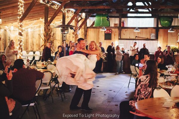 Groom carrying the bride in during the Grand March of the Bridal Party at Weddings in Echo Valley....