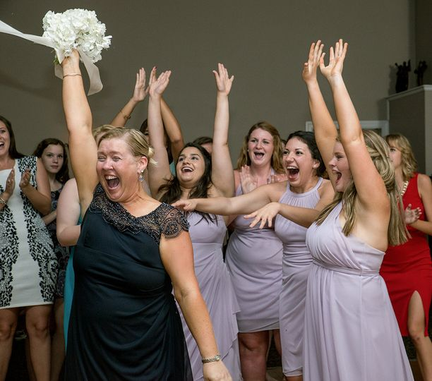 the mother of the bride catches the bouquet at a w