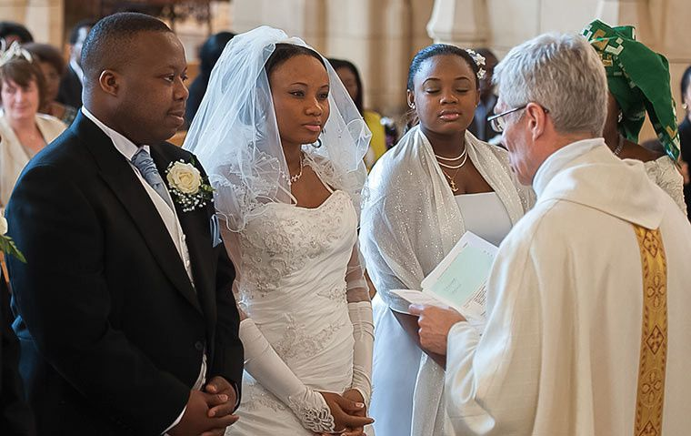 Bride and groom with the priest