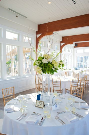 Tall wedding centerpiece of roses, hydrangea, peonies, orchids and curly willow