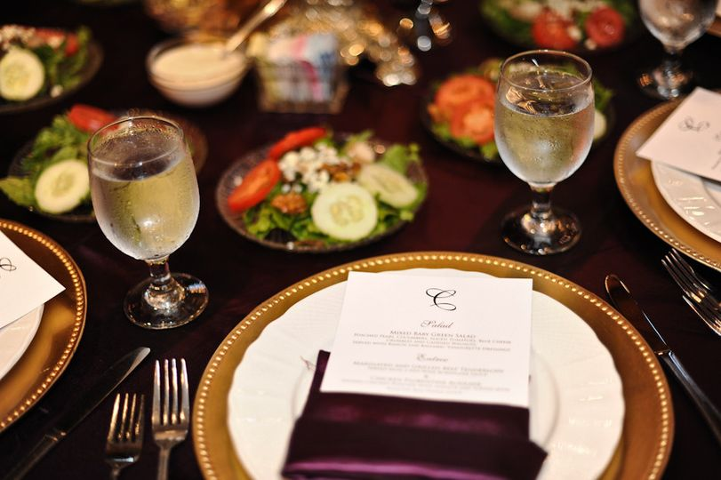 Table setting with pre-set water glass, napkin, plate, charger, flatware and garden salad.