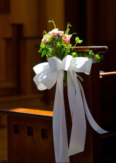 Floral decor and ribbon on aisle pew