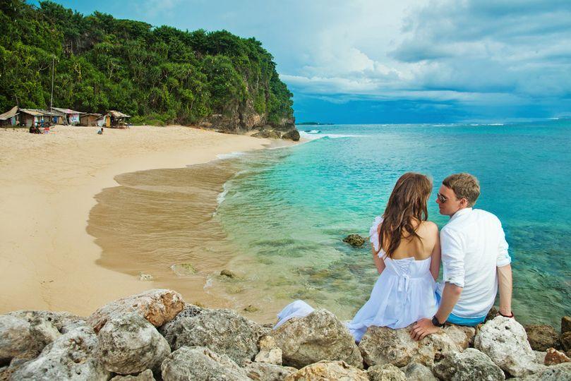 couple kissing rocks beach