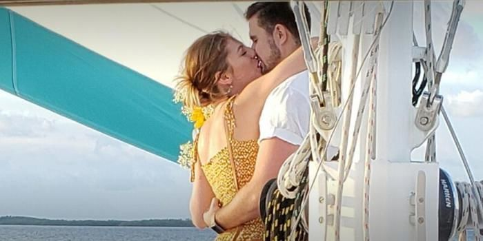 Newlyweds kiss on the boat