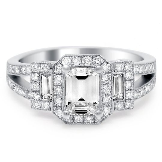 Stunning emerald cut halo diamond ring has a diamond encrusted split shank and side baguettes.