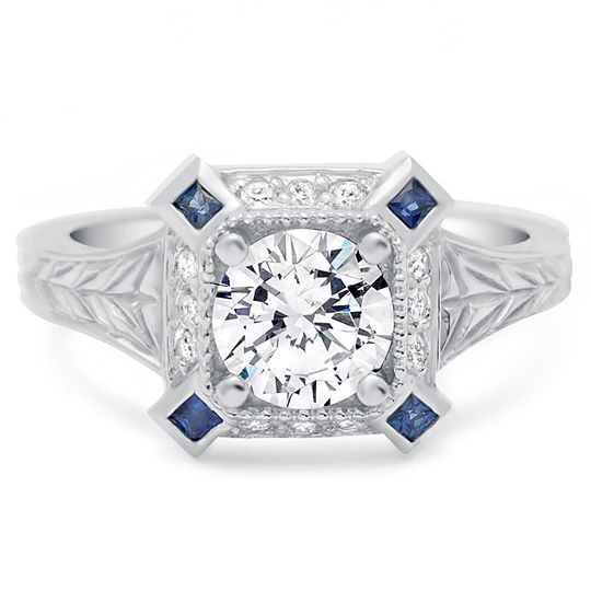 Vintage inspired engraved ring has a round diamond center and 4 princess cut blue sapphires in each...