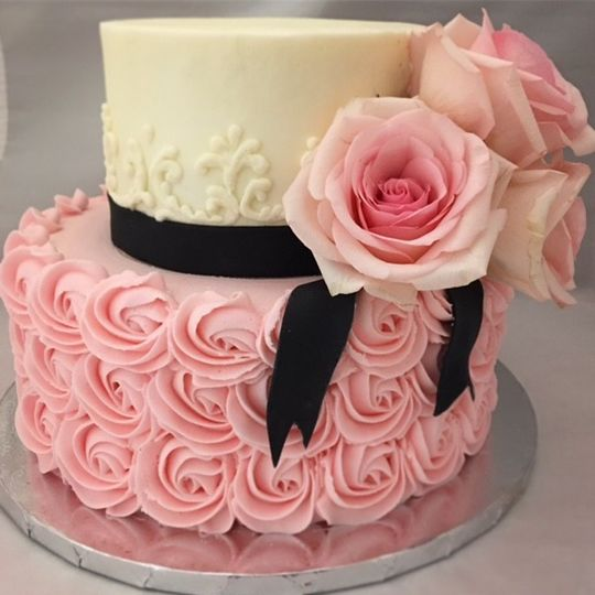 Pink rose themed cake with black ribbon