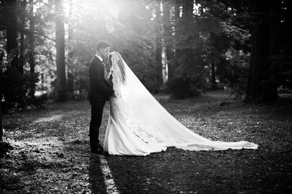 portrait of bride and groom in forest with veil
