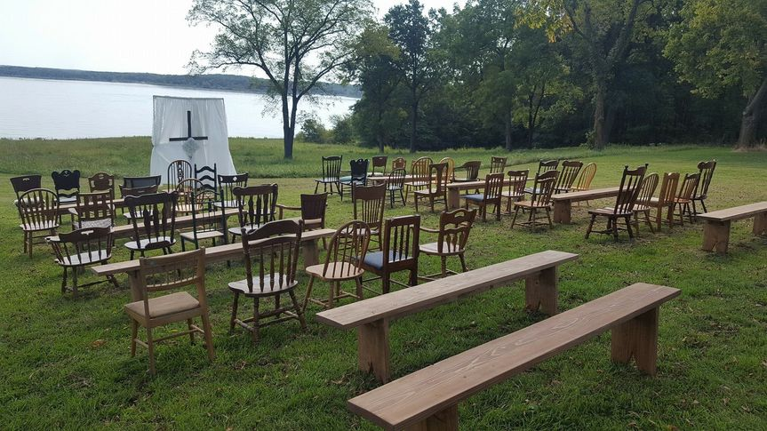 Lakeside ceremony with a mixture of antique seating and wooden benches