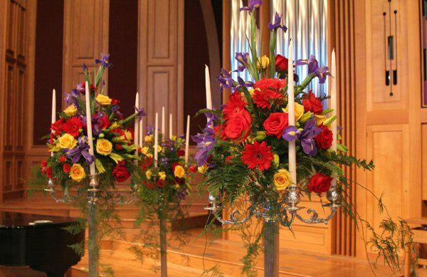 Candelabra arrangement has gerbera daisy, calla lily and iris.