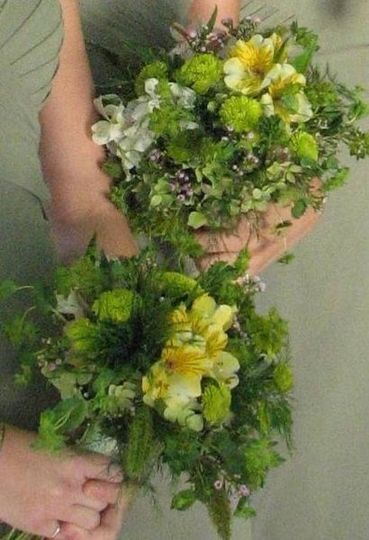 Bridesmaids bouquets made with Green roses, green buttom pom, yellow and white alstromeria and some...