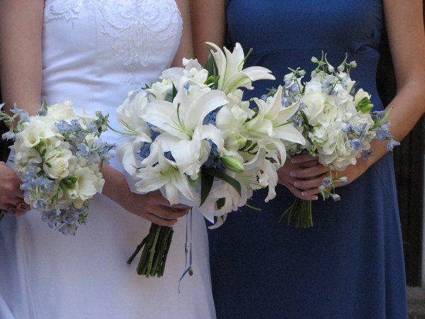 Brides Bouquet: Blue hydrengia, white roses, white stargazer lilies, and freesia Bridesmaids: white...