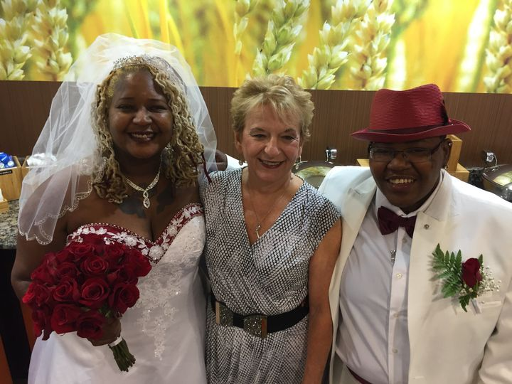 Couple posing with officiant