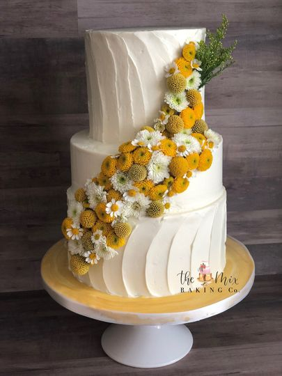 Modern floral cascade against textured buttercream with varying height tiers