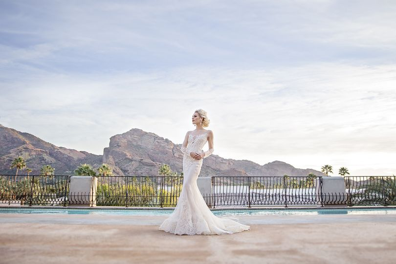 Bride in an elegant sleeved dress by the poolside