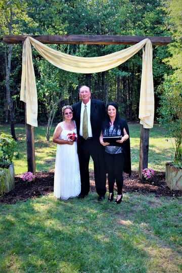 Newlyweds and officiant under the arch