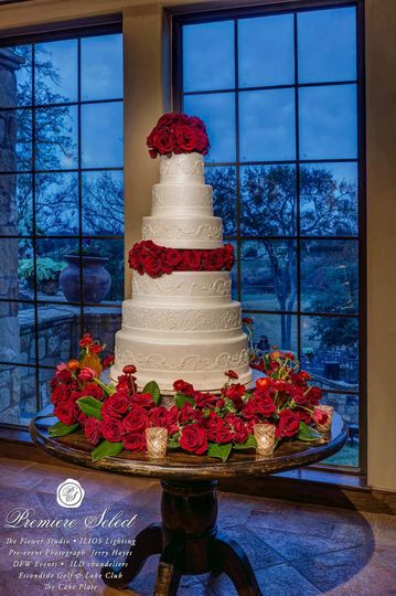 Red roses and ranunculus flowers adorned this beautiful wedding cake for a spectacular display