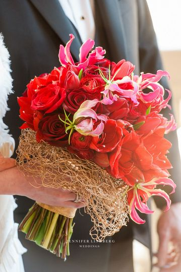 Red amaryllis and gloriosa lilies look incredible in this bouquet