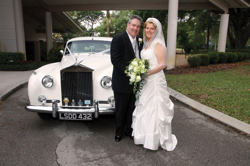 Newlyweds by the wedding vehicle