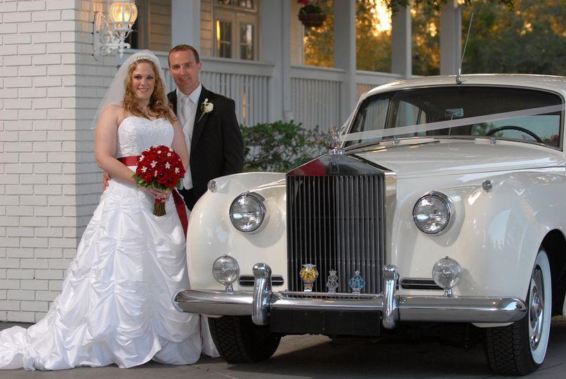 Bride and groom beside their wedding car