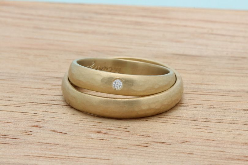 Classic half round bands in recycled 18k yellow gold. With a hammered texture and a flush set...