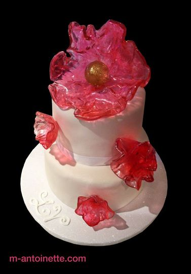 "Two-tiered cake decorated with translucent pink sugar glass ""flowers"""