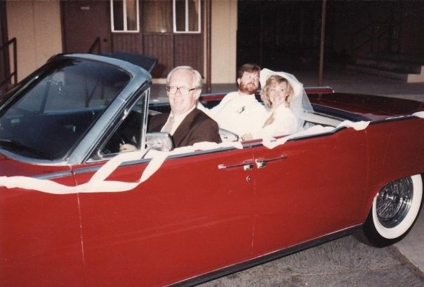 Officiant and couple in a car