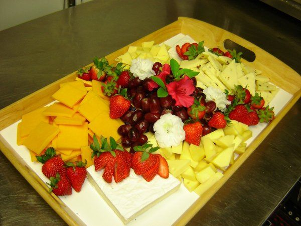 A delicious mulit-cheese platter garnished with grapes and strawberries.