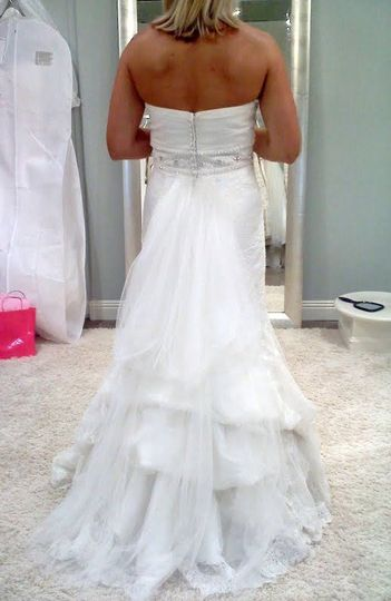 The bustle on this Allure gown is a single pick-up to show case the skirt full of organza flowers!
