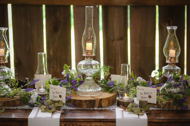 Repurposed oil lamps and silk flower garlands served as tabletop decor in this barn reception.