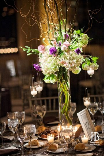 Tall centerpiece with hydrangea, viburnum, lisianthus, roses, branches and hanging votives