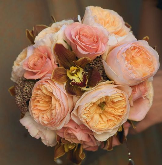 Antique roses in blush and peach accented with chocolate orchids.