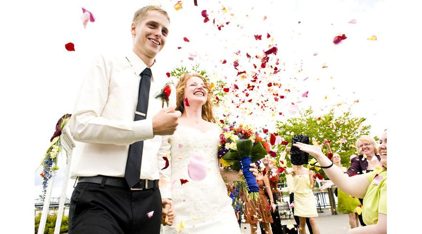 Happy newlyweds being showered with flower petals