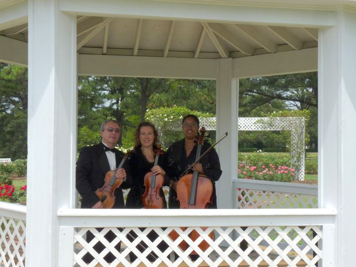 String trio standing in gazebo